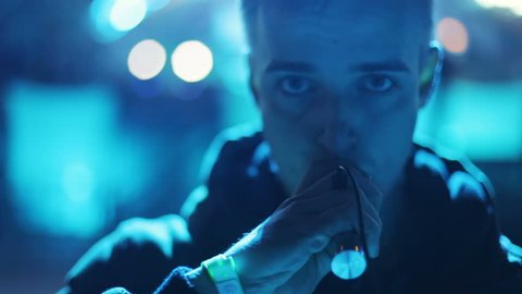 young man smoking electronic cigarette closeup portrait front view blue light night looking camera drug confident cool smoke unhealthy habit youth lifestyle smoker vapor fume e-cigarette caucasian guy