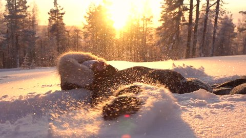 SLOW MOTION Happy girl in warm winter clothing doing snow angels in fresh powder blanket. Cheerful woman laying in powder snow, making angle at sunrise. Playful girl enjoying winter, snowflakes flying