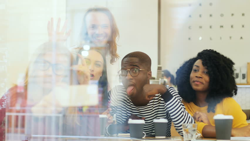View through window of a mixed group of people sitting in the coffee shop and taking a selfie over coffee, making funny face and enjoying time together. | Shutterstock HD Video #32123641