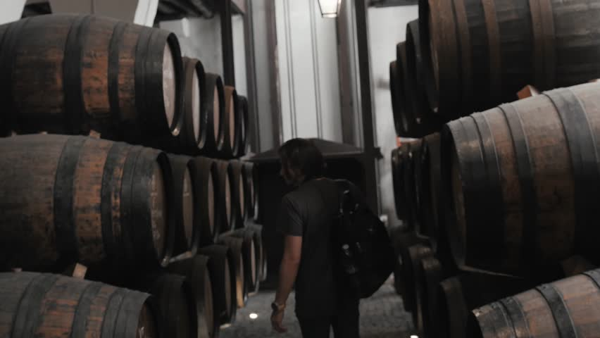 Old wine barrels in a wine cellar, sommelier man tourist dicover, porto, portugal, old factory stock