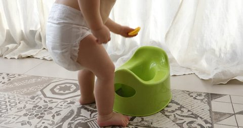 Baby and chamber-pot. Toddler play from the pot in interiors