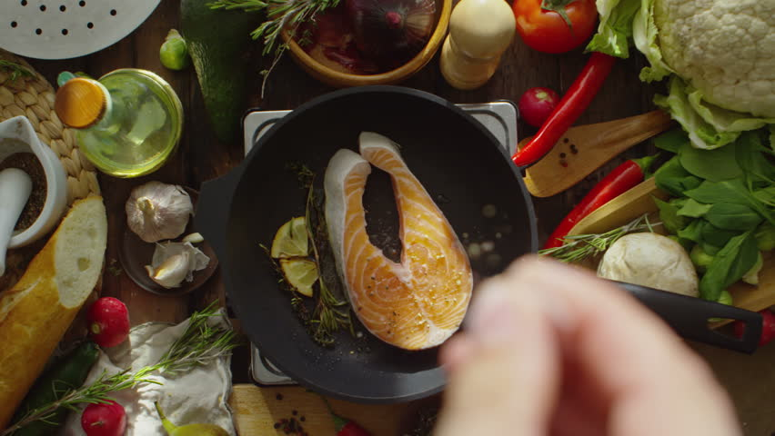 Cinemagraph of male hand adding seasonings to salmon steak frying on pan with lemon and herbs