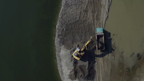 Yellow dredge scooping sand in river and loading tipper on sandbank, aerial view, extreme high angle, top shot,  drone flying to digger and dump truck, sunny day