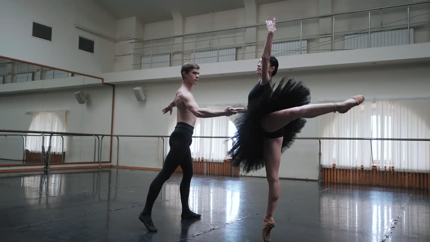 Young man practicing in classical ballet with young beautiful woman in black tutu clothing in the gym. he carrying the girl on shoulders Minimalism interior, sensual dance. Slow motion