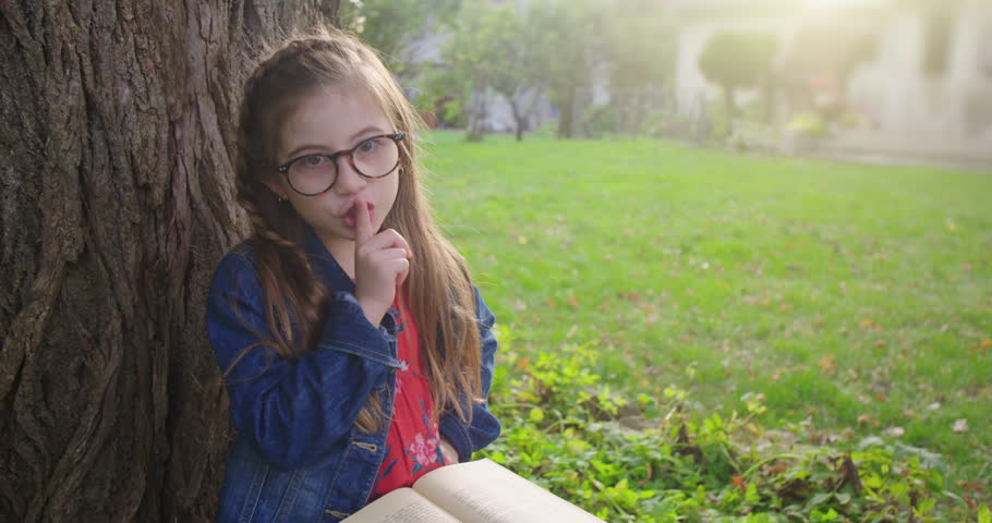 Young Girl with Book Shushes at Camera to be Quiet. a lowering shot towards a little girl with glasses reading a book under a tree when she turns to camera and shushes to be quiet