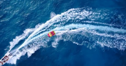 v09310 People enjoying boats and watersports with view from aerial flying drone in clear aqua blue sea water and blue sky