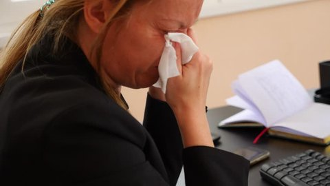 Sick business woman with flu blowing nose in tissue. in the office. 4k, slow motion