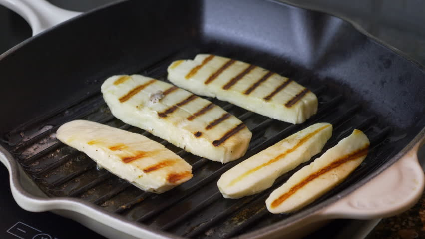 Halloumi cheese frying in grill pan. Grilled slices of halloumi cheese frying in grill pan. Close up indoors. Cyprus goat cheese fried.