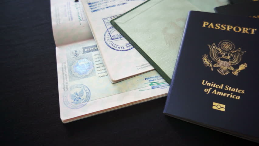 Panning shot of passports from USA, Mexico, Canada and Germany with visa and entry or departure stamps.
