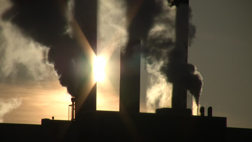 Fumes billow out of a giant smoke stack against the sunny sky (High Definition)