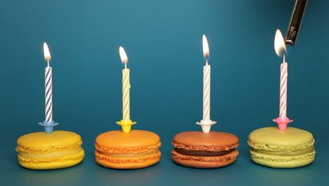 Macarons with candles arranged horizontally.