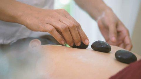Dolly Shot of Beautiful Asian woman Enjoying Hot Stone Massage Treatment
