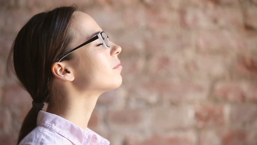 Young woman wearing glasses inhaling and exhaling fresh air, taking deep breath, enjoying practicing breathing pranayama exercises indoors, calming down, reducing stress, close up face side view | Shutterstock HD Video #32239261
