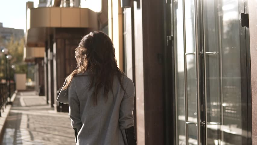 Back View Of Young Businesswoman Talk On Mobile Phone And Going To