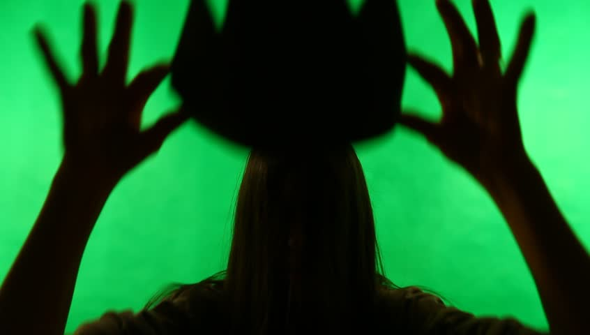 Young adult woman queens or crowns herself against green screen chroma background. Back-lit silhouette.