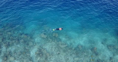 v11897 many people young boys girls snorkeling over coral reef with drone aerial flying view in crystal clear aqua blue shallow water