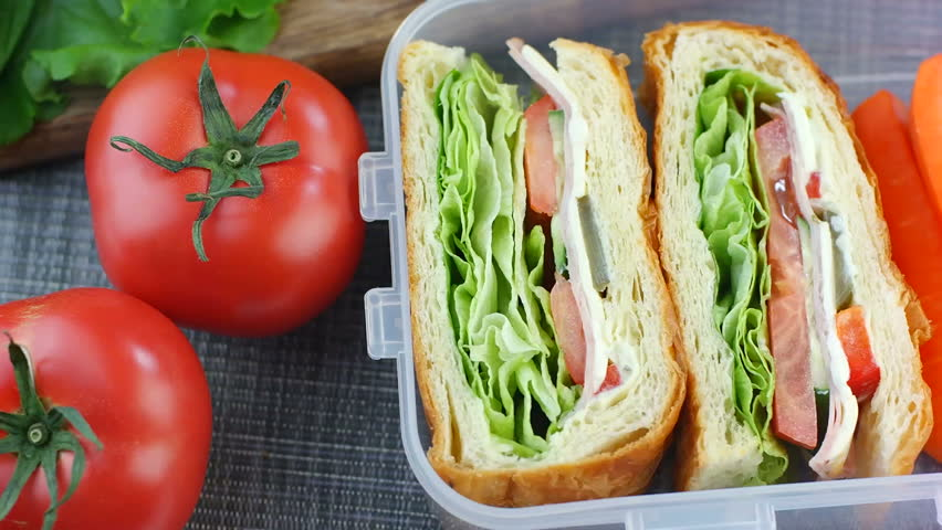 Fresh made sandwiches with carrot sticks in the lunch box, ready to eat, dolly shot, top view