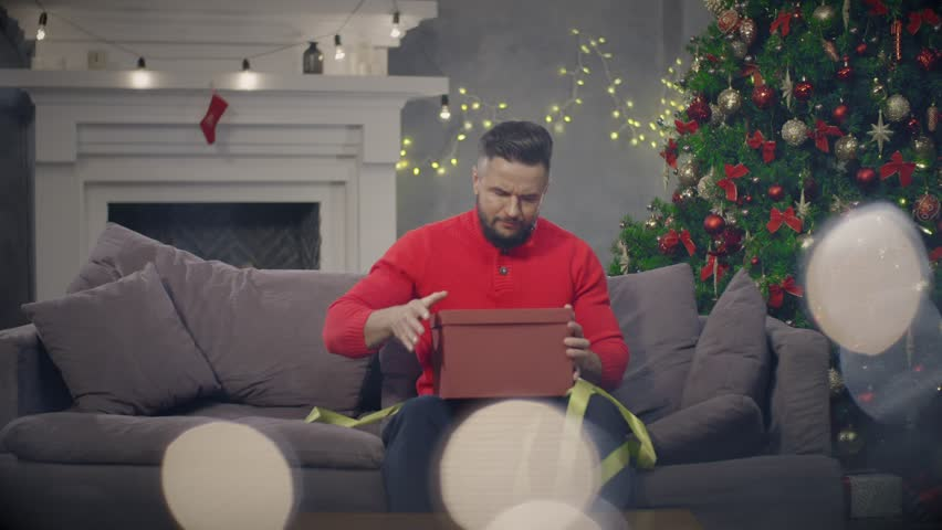 Young man open Christmas present sitting on couch. Frustrated man in holiday eve