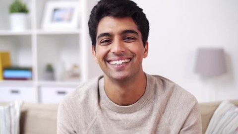 emotion, expression and people concept - portrait of happy smiling young indian man at home