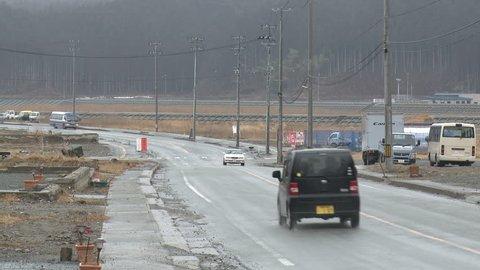 RIKUZENTAKATA, JAPAN - CIRCA MARCH 2012: Cars driver through remains of tsunami hit town one year after disaster
