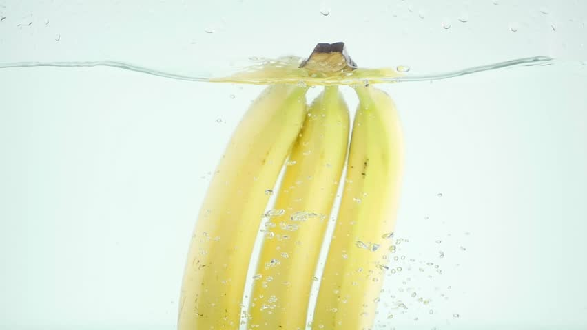 Bananas plunging into water on white background in slow motion #32332711