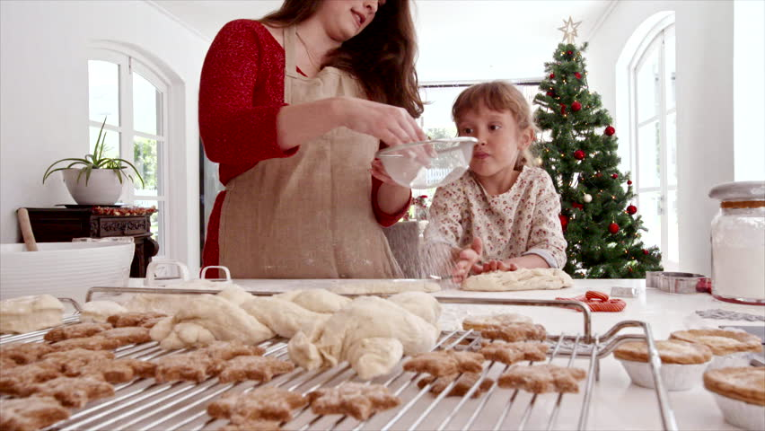 Smiling young woman with little girl sprinkling flour on dough. Mother and daughter preparing Christmas cookies.