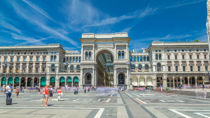 The Galleria Vittorio Emanuele II timelapse hyperlapse on the Piazza del Duomo (Cathedral Square). This gallery is tourist attraction of Milan. Blue cloudy sky at summer day. People walking on the
