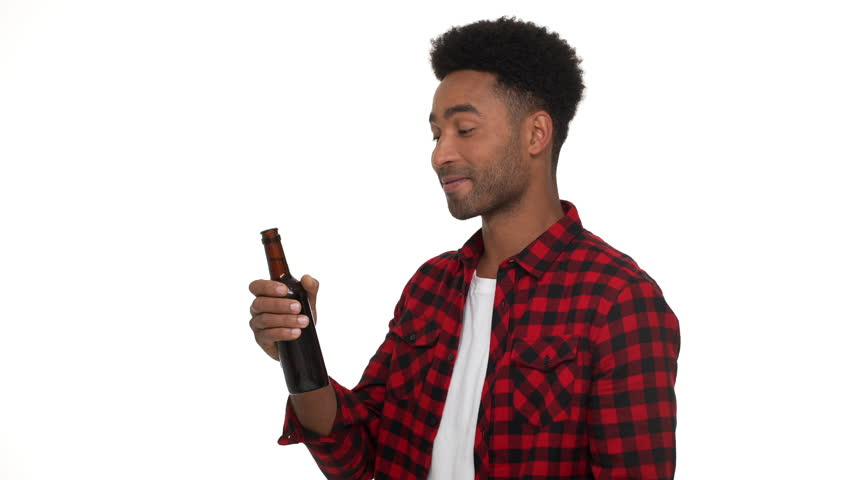 half-turn portrait of handsome dark-skinned man in casual trendy clothes enjoying alcohol beverage drinking beer from glass bottle with pleasure over white background. Concept of emotions