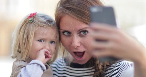 Millennial Mother taking selfie with daughter
