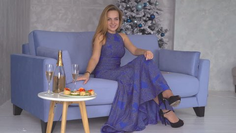 0966025816 beautiful sexy blonde in a luxurious long blue dress in rhinestones sits on  a sofa in