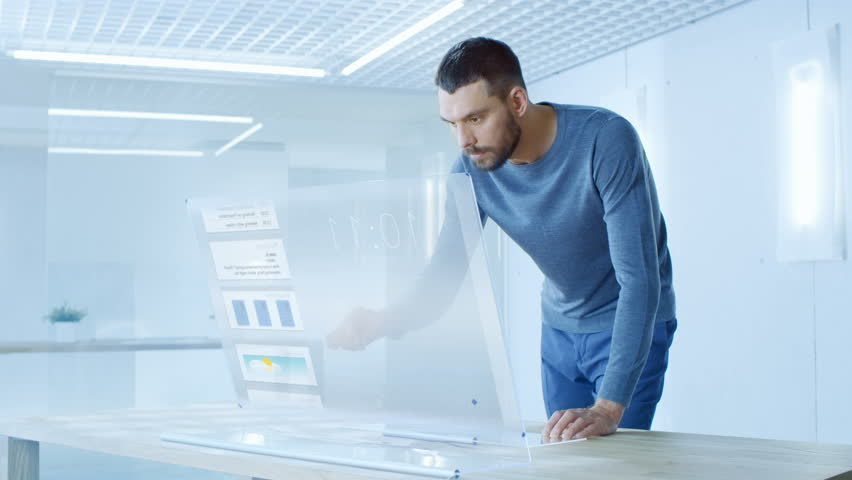 In the Near Future Stylish Man Logins in His High-Tech Computer with Transparent Display and Checks Useful Work Related Statistics. He Works in the Ultramodern Light Office. 4K UHD. | Shutterstock HD Video #32413111