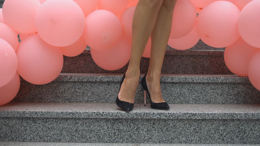beautiful female legs in black high-heeled shoes. the woman is standing on the steps against the background of a large number of balloons.