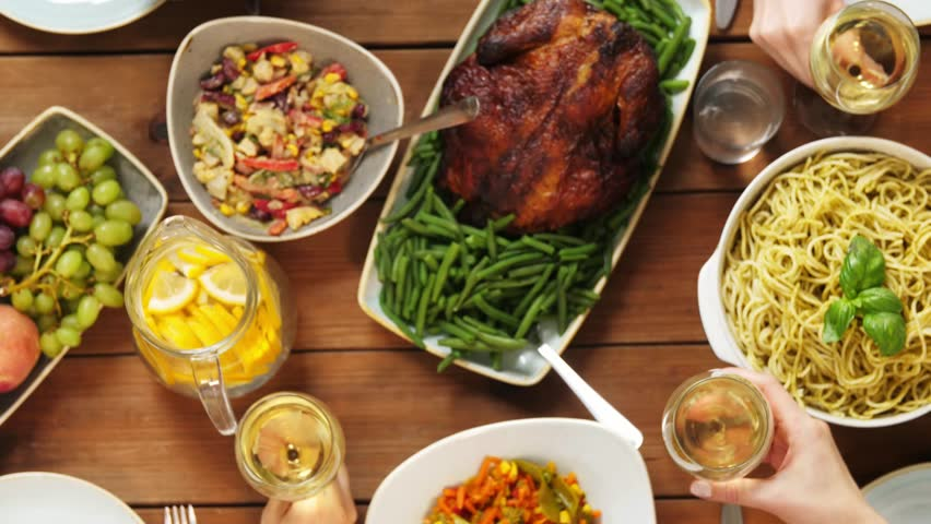 eating and holidays concept - group of people at table with food clinking wine glasses #32420191