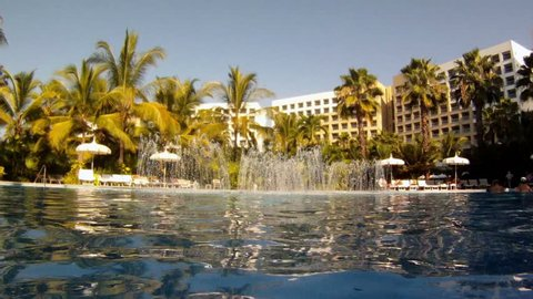 Tropical resort swimming pool hotel.Resort hotel complex in Puerto Vallarta, Mexico. Beautiful swimming pools, lush tropical botanical gardens and waterfall fountains. Palm trees and flowers.