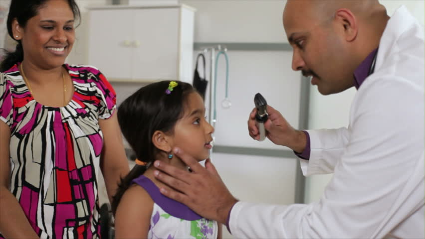 An Indian pediatrician or family doctor listens to the heart of a little girl who is being accompanied by her mother. | Shutterstock HD Video #3243385