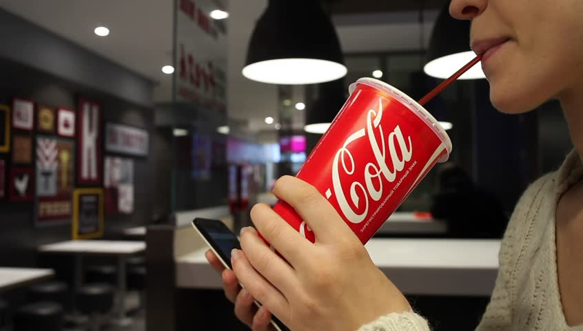 MINSK, BELARUS - october 30, 2017: Coca-Cola soft drink. Woman drinks a Coca-Cola and uses a smartphone on a cafe. Coca-Cola is a carbonated soft drink sold in stores, throughout the world.