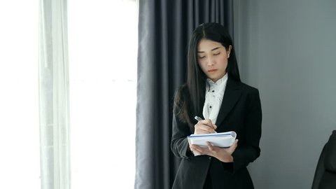 business woman standing write note thinking in intuitive way on office