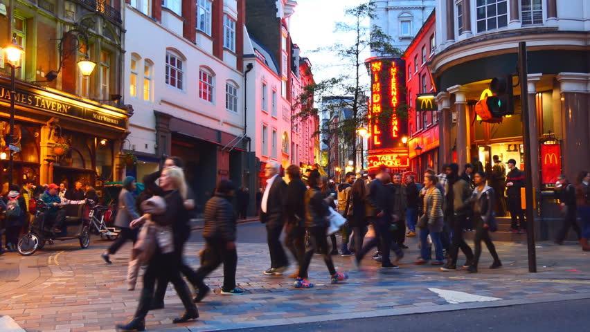 LONDON, ENGLAND, UNITED KINGDOM - APRIL, 2017: Night life of London Soho. People crossing illuminated Great Windmill street, Windmill International strip club, rickshaw drivers waiting for passengers