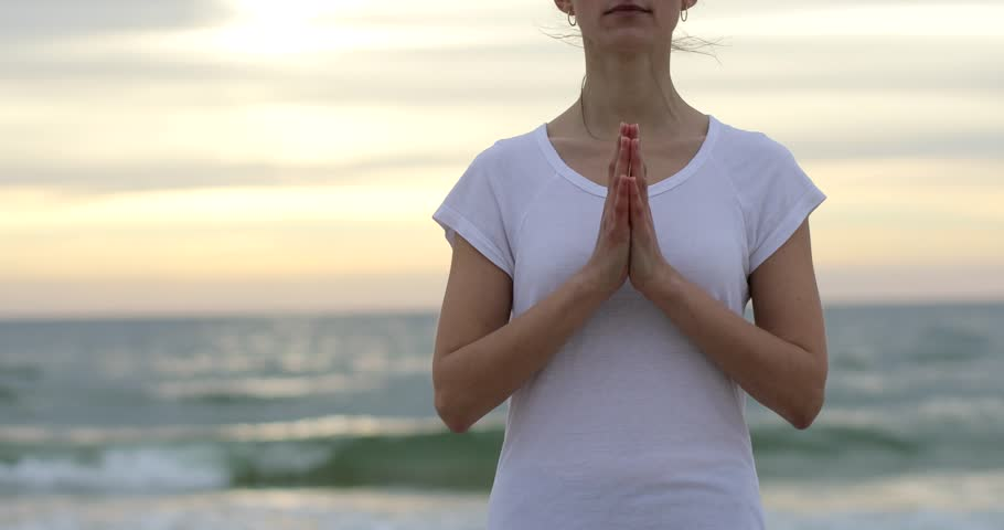 Yoga woman practices heart opening lotus mudra with hands clasped together no face close up 4k at sea ocean waves background. Doing healing moves with palm fingers at sunset. Namaste wish pray concept