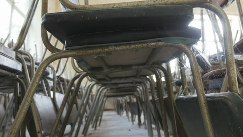 Rows of old chairs stacked on top of each other in an abandoned restaurant, public dining room, conference room. Underside view