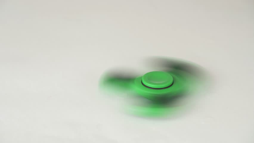 Green fidget spinner is spinning on a white background stock footage video   Shutterstock HD Video #32491651