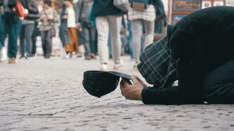 CZECH REPUBLIC, PRAGUE, SEPTEMBER 12, 2017: Homeless Beggar Man with a Hat on the Sidewalk Begs for Alms from People Passing by in Prague, Czech Republic. Slow Motion in 96 fps. Feet of crowd people