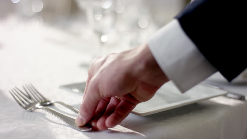 Shot of waiter hand correcting cultery on table before celebration at banquet hall | Shutterstock HD Video #32506471