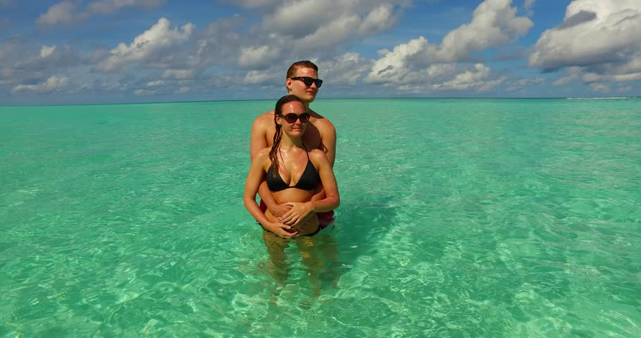 v15526 two 2 people together having fun man and woman together a romantic young couple sunbathing on a tropical island of white sand beach and blue sky and sea
