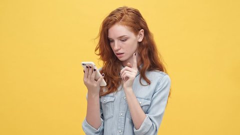 Happy surprised ginger woman in denim shirt using her smartphone over yellow background