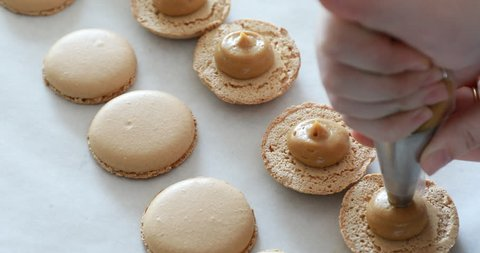 Making Caramel Macarons : hand with confectionery bag squeezing cream filling to macarons shells
