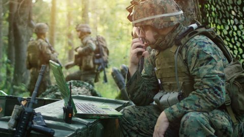 Military Staging Base, Chief Army Engineer/ Signalman Uses Walkie-Talkie Radio and Army Grade Laptop. Squads Resides in Camouflaged Tent While Being on Reconnaissance Operation/ Mission. 4K UHD.