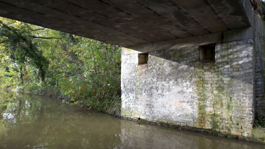 Ripples of water reflecting on the underside of a canal bridge.