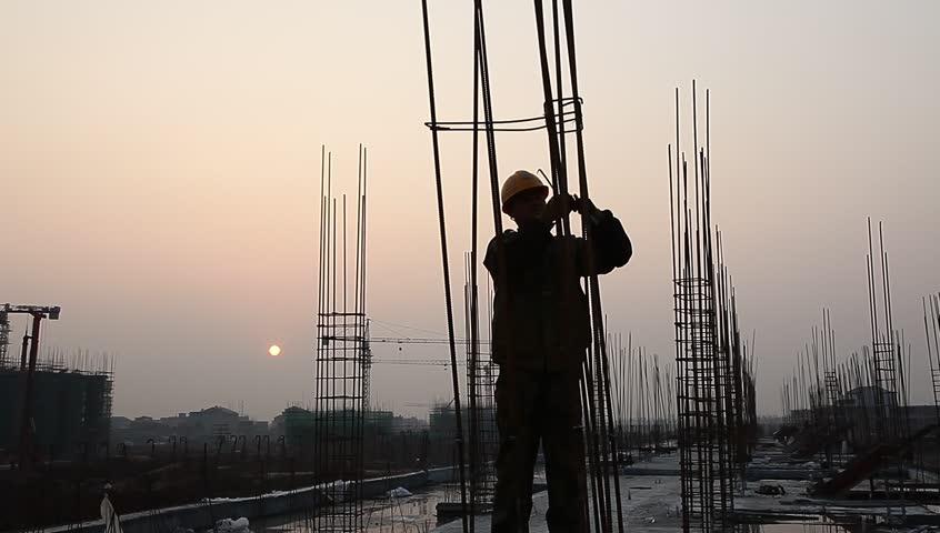 Worker working with concrete reinforce iron near sunset | Shutterstock HD Video #3259351