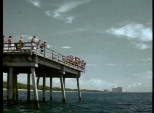 Stuntman driving motorcycle off pier into ocean